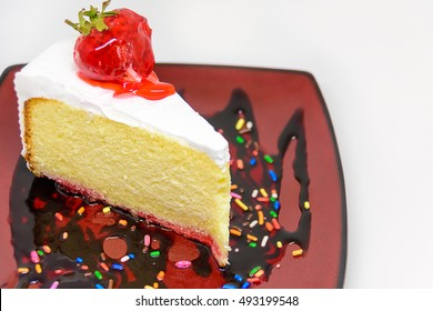 Sweet cake slice with strawberries topping isolated on white background / selective focus