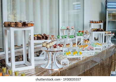 Sweet cakes at a wedding banquet. Catering, sweet festive buffet. Candy bar