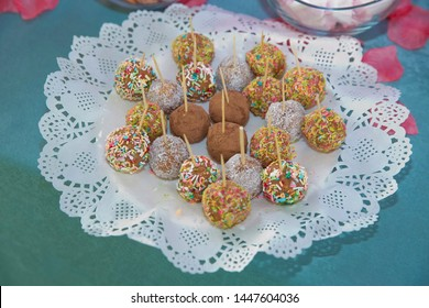 Sweet candies on the dessert table . Balls of biscuit on a stick loli pop. cake pop. candy bar . Delicious and tasty dessert table with cupcakes . little coloured cakes on the plate for holiday party