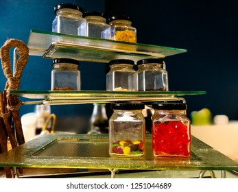Sweet candy in glass bottles on glass sheet for design interior vitage dark background