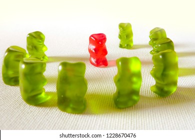 sweet candy gummy teddy bears representing group of students or work colleagues bullying and mobbing helpless victim in harassment and abuse social problem concept isolated on white background