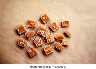 Sweet caramel candies background. Salted caramel pieces and sea salt close up, top view over brown baking paper.