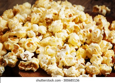 Sweet caramel popcorn in a wooden bowl, selective focus