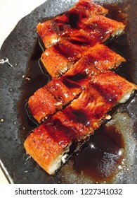 Sweet caramelized sauce drizzled over perfectly grilled freshwater eel, or popularly known as unagi or Japanese eel, served on a black plate.