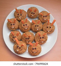 sweet carrot muffins with easter bunny decor, made of chocolate drops, carrot sticks and hazel pieces