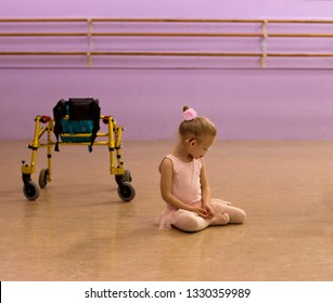 Sweet Caucasian little girl wearing hearing aid, glasses, a bun and pink ballet leotard sits next to her gold walker mobility aid in ballet studio