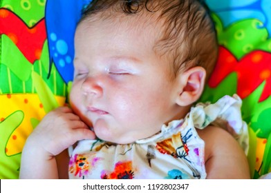 Sweet Caucasian newborn girl sleeping on a bed with colorful linens. Beautiful infant girl asleep.
