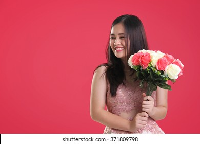 Sweet cheerful Asian teenage girl with natural smile holding a bouquet of roses, looking sideways at copy space on pink background for Valentines Day