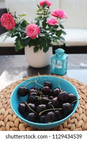 Sweet cherries in a blue bowl on a table. Close up. Fresh berries on a table. Cat on a background