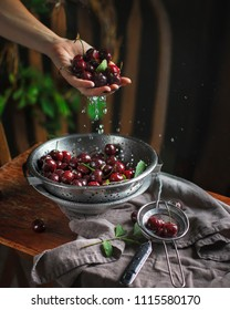 Sweet cherries on the nature rustic background, summer, woman's hand