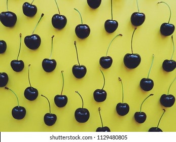 Sweet cherries on a yellow background. Cherry pattern.