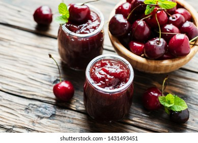 Sweet cherry jam in the glass jar, selective focus and rustic style