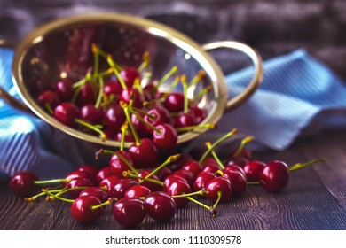 sweet cherry on the table close-up. background with sweet cherry and colander. sweet cherry is on the table, a napkin and a colander.