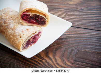 sweet cherry strudel of puff pastry; two slices on plate