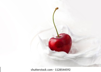 Sweet cherry in yogurt. Close-up milk or cheese dessert with cherries. One fresh cherry on a twig, white yogurt mass