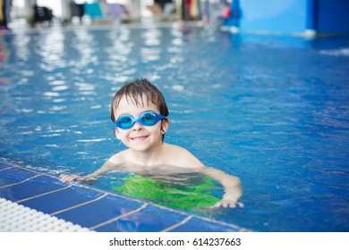 Sweet child, boy, playing in water world playground, enjoying attractions, swimming in a big swimming pool on a holiday