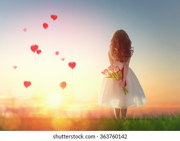 Sweet child girl looking at red balloons. Little child girl holding bouquet of flowers. Balloons in shape of heart flying in the sunset sky. Wedding, Valentine, love concept.