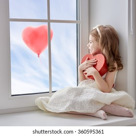 Sweet child girl with red heart. Little girl sitting on the window and holding gift box. Wedding, Valentine concept.