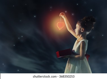 Sweet child girl with red heart. Happy little girl with gift box on background of star sky. Wedding, Valentine, celebration concept.