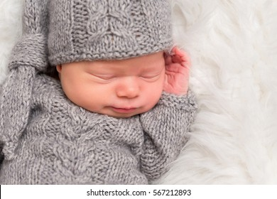 Sweet child in a hat napping all enveloped with a gray blanket, closeup