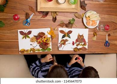 Sweet children, boy brothers, applying leaves using glue while doing arts and crafts in school, autumn time