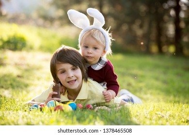 Sweet children, boy brothers with bunny ears, egg hunting for Easter, child and Easter day traditions. Kids and holidays