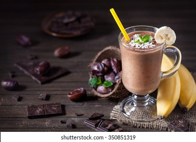 Sweet chocolate banana smoothie with coconut milk and dates decorated with mint leaves on wooden background