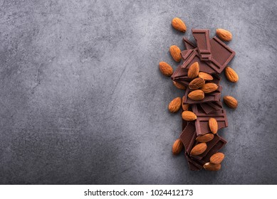 sweet chocolate bars with almond on a stone table, top view