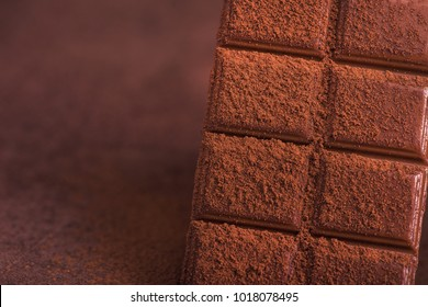 sweet chocolate bars with cocao powder on a table