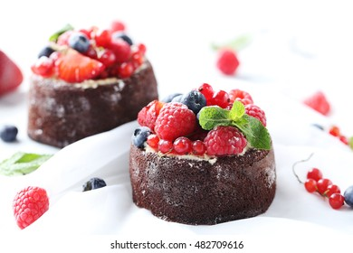 Sweet chocolate cakes with berries on white background