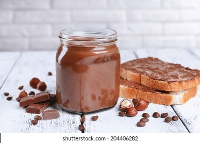 Sweet chocolate cream in jar on table on light background