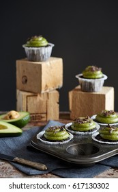 sweet chocolate cupcakes with avocado cream and grated chocolate on wood cubes in the dark grey background