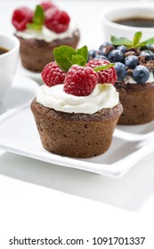 sweet chocolate cupcakes with fresh berries for dessert, vertical, closeup