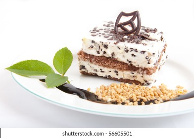 Sweet chocolate dessert with nuts and chocolate on white plate