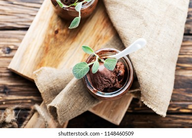 Sweet chocolate ice cream with sage on the wooden table, selective focus