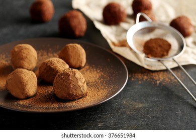 Sweet chocolate truffle on a black wooden table