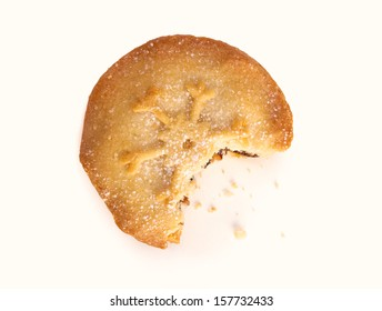 A sweet Christmas mince pie with a bite out of it on a white background.