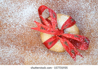 Sweet Christmas mince pie with a red ribbon tied round it on a wooden cooling board with icing sugar.