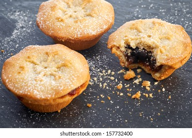 Sweet Christmas mince pies on a Slate cooling board with a bite missing from one.