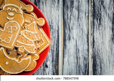 Sweet Christmas pastries. Spicy gingerbreads on red on a plate on a wooden table.