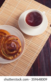 Sweet cinnamon bun and cup of hot tea on wooden background