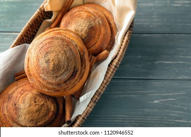 Sweet cinnamon buns in wicker basket on table