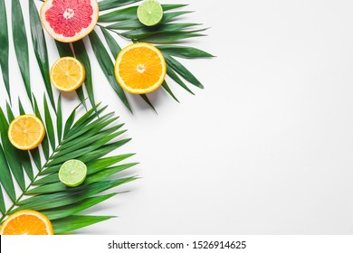 Sweet citrus fruits with tropical leaves on white background