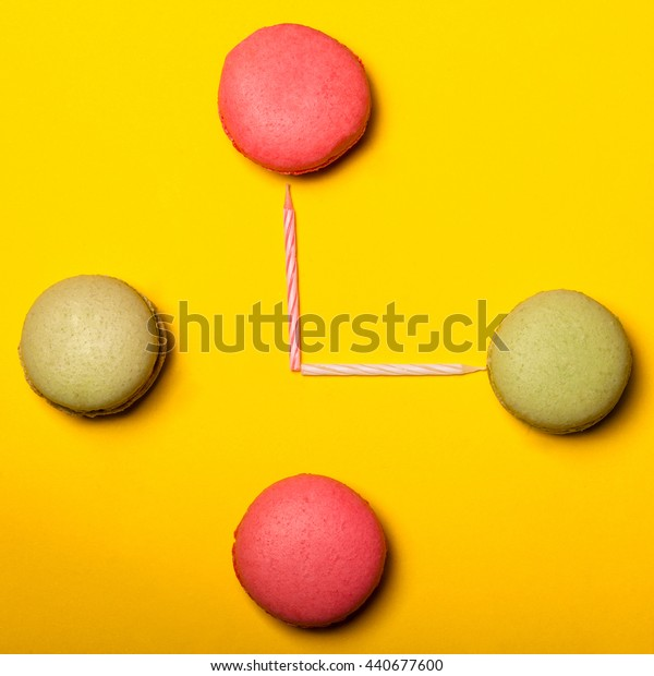 Sweet clock made of pink and green macaron with candles on yellow background