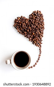 For a sweet coffee break. A heart made of coffee beans flying like a little balloon from a cup on a white background.