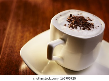 Sweet coffee with cream and chocolate flakes, in an elegant white cup with saucer, on wooden table