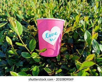 Tasse de café sucrée à la lumière du soleil à l'extérieur. Arrière-plan vert clair et paysage de jour ensoleillé. Sticker en forme de coeur avec laisser l'amour vous aimer.