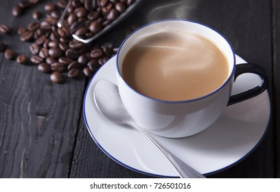 Sweet coffee in white cup with coffee spoon