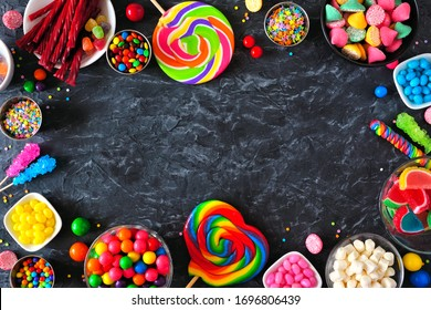 Sweet and colorful candy buffet frame. Top view table scene over a dark stone background Copy space.