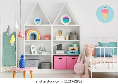 Sweet colorful decorations and white furniture in a fun kid's bedroom interior with a pastel pink rabbit pillow